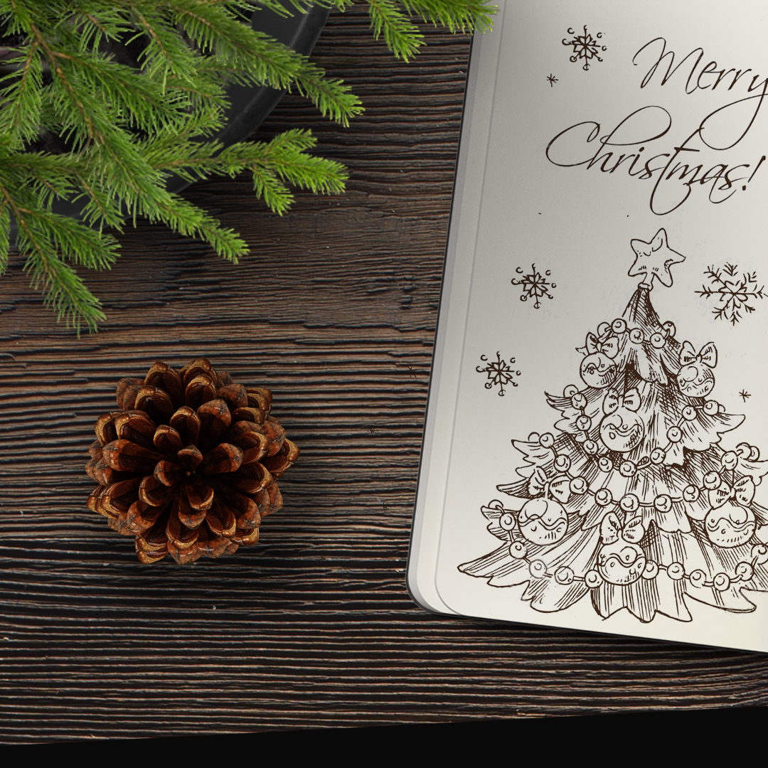 A drawn christmas tree in a notebook and a pine cone